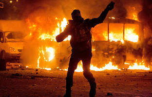 [A protester throws stones at a burning police bus in Kiev, Ukraine.